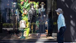 Mujer en Estados Unidos mirando el aparador de una tienda de ropa, durante la pandemia.