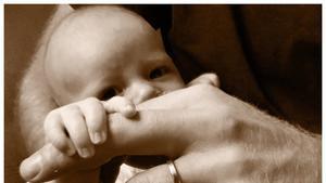 Archie Harrison coge el dedo de su padre, el príncipe Enrique.