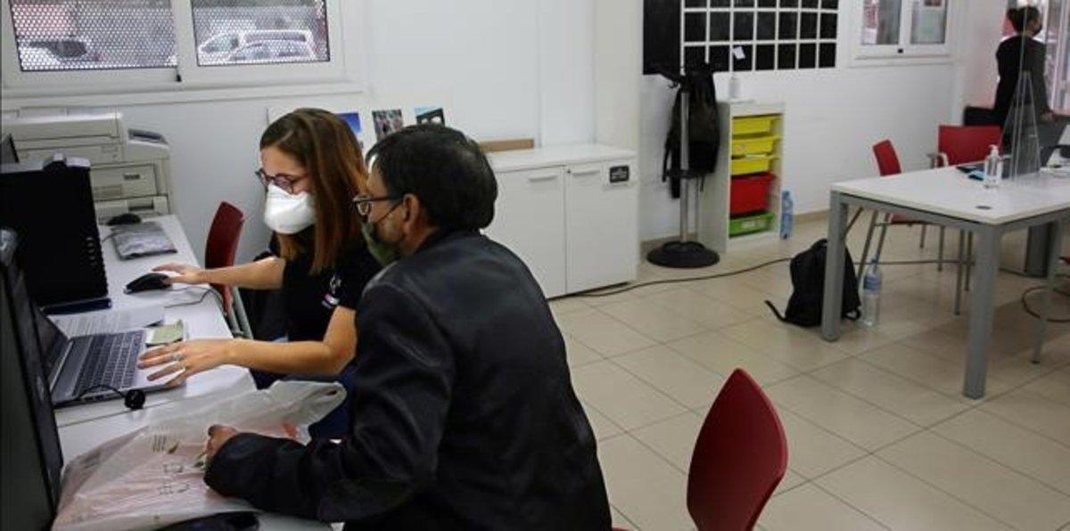 Una agente de apoyo digital del ayuntamiento junto a un usuario, en el casal del barrio Besòs-Maresme.