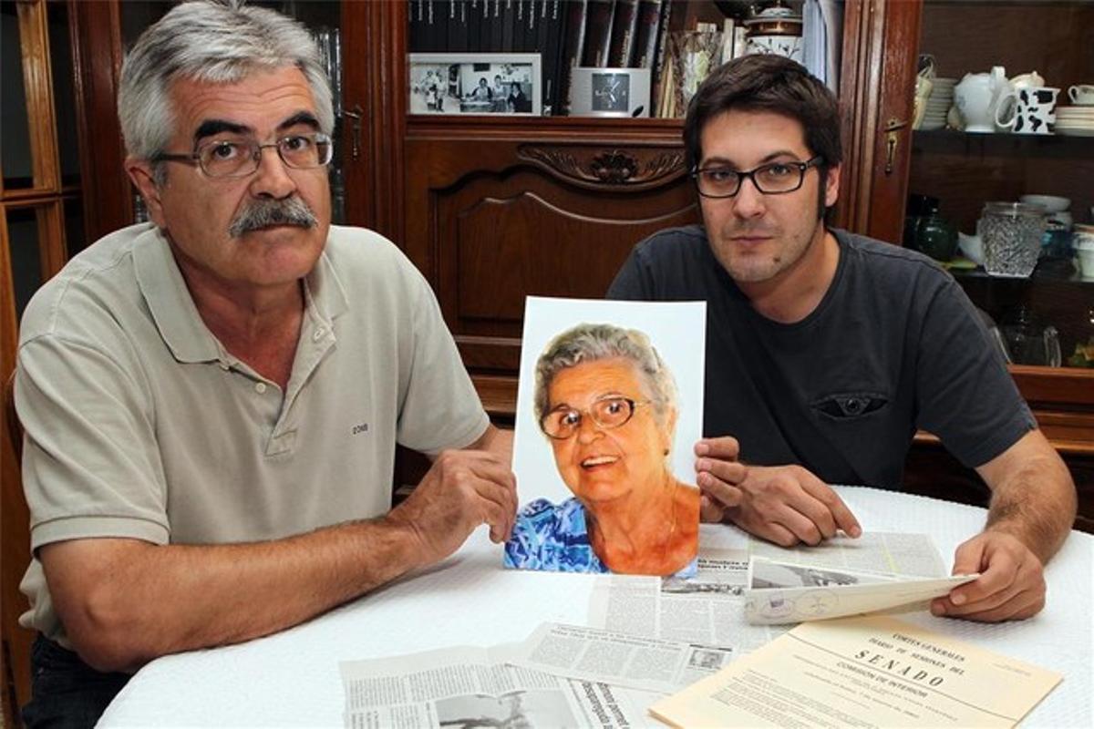 Joaquim Teixidor, junto a su hijo, muestra una foto de su madre, Maria Poch, desaparecida en el 2004.