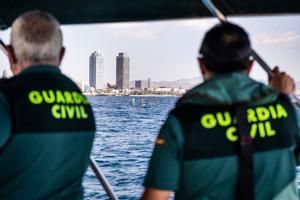 Agentes de la Guardia Civil vigilan la pesca ilegal ante una playa de Barcelona.