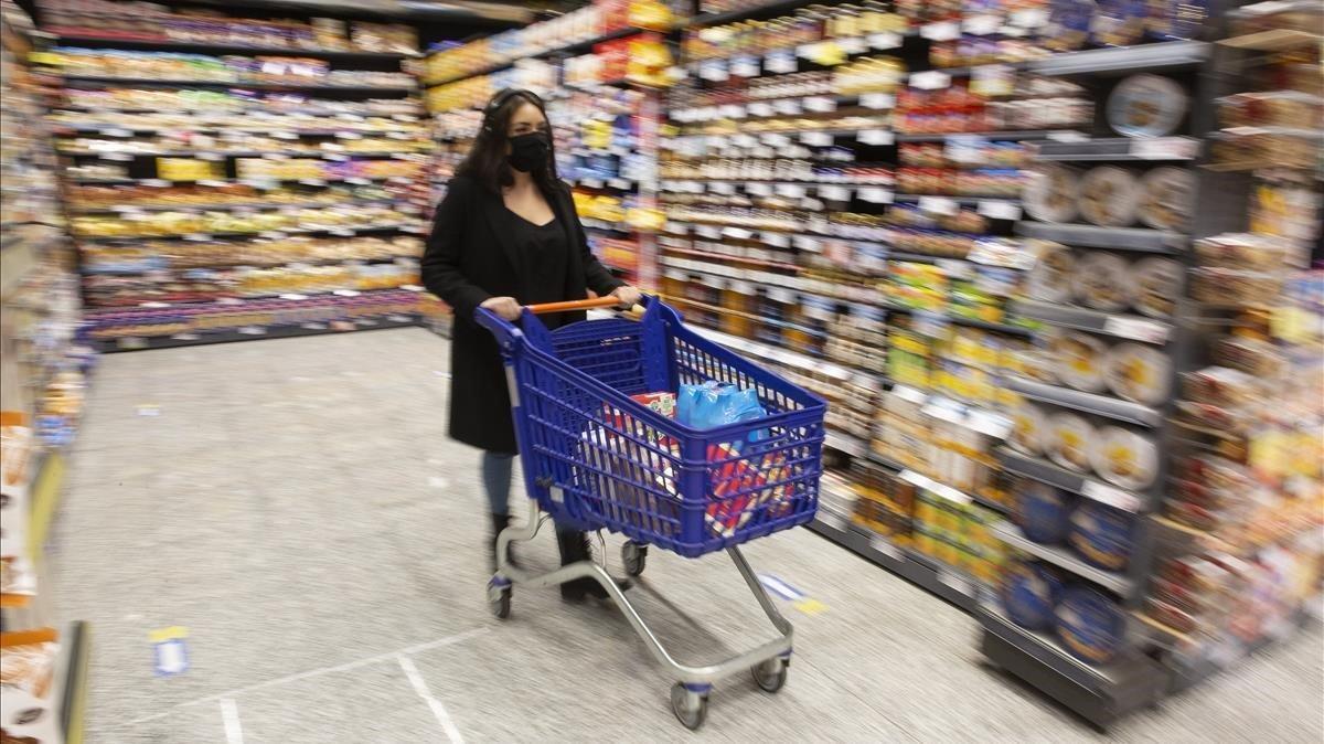 Una espectadora sigue las instrucciones de la 'Audioguia per a supermercats en temps de pandèmia' en un súper del Eixample.