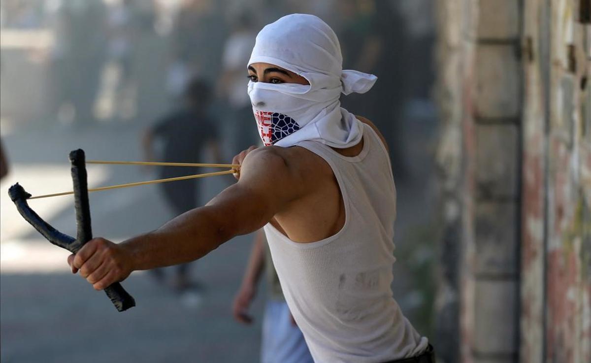 Un manifestante palesino lanza piedras a las fuerzas israelís durante las protestas en Hebrón