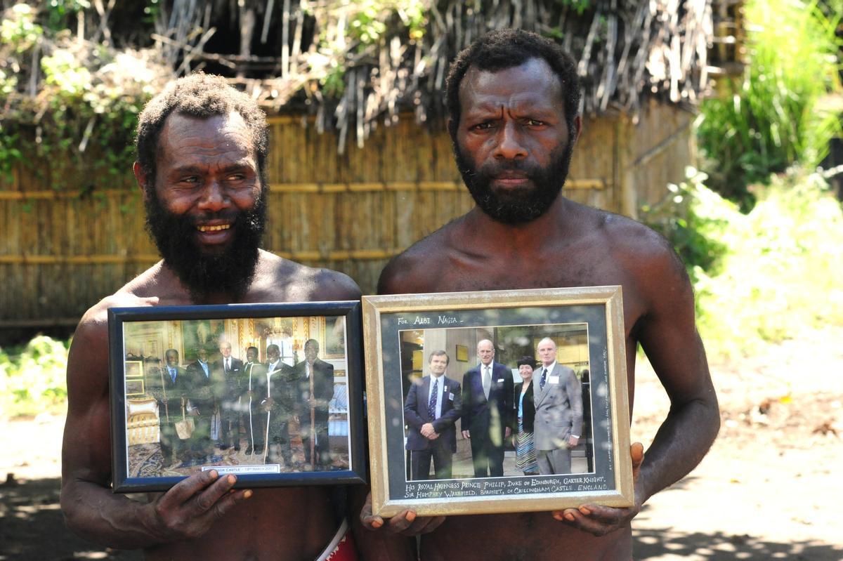 Dos miembros de una tribu en Yaohnanen muestran fotos enmarcadas de su visita en 2007 con el Príncipe Felipe de Edimburgo, su dios