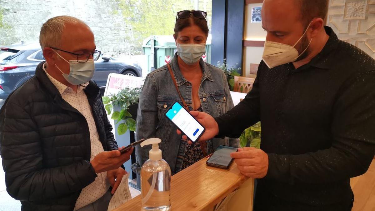 Dos clientes muestran sus certificados COVID-19 para entrar en un local