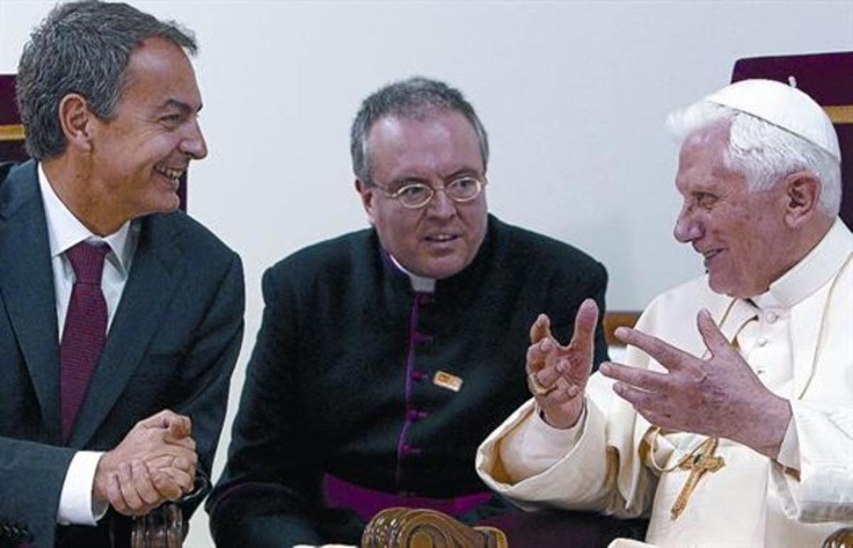 Zapatero y Benedicto XVI conversan, con ayuda de un intérprete, ayer en el aeropuerto de El Prat.