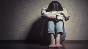 Una mujer oculta su rostro, sentada en el suelo.