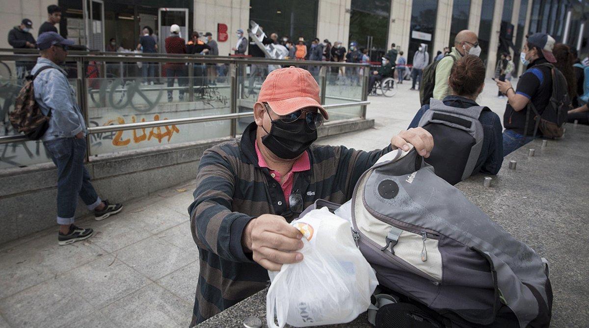 Colapara recoger artículos de primera necesidad que distribuye el Banc dels Aliments, enel SAIER de Barcelona, el 9 de mayo.