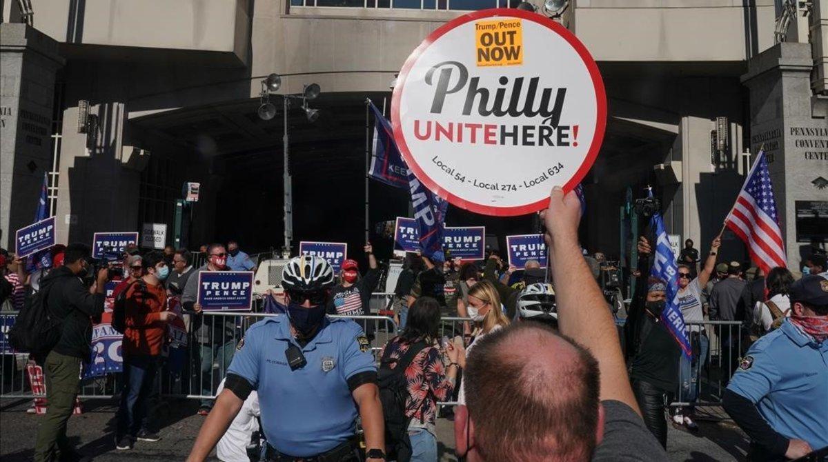 Un manifestante muestra un cartel frente a los partidarios de Trump a las puertyas del Centrode Convenciones de Pensilvania, en Filadelfia.