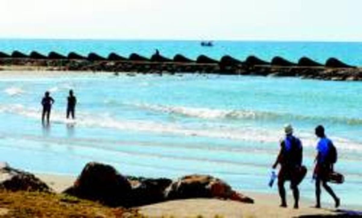 Bañistas junto a uno de los espigones de las playas de Cunit, ayer.