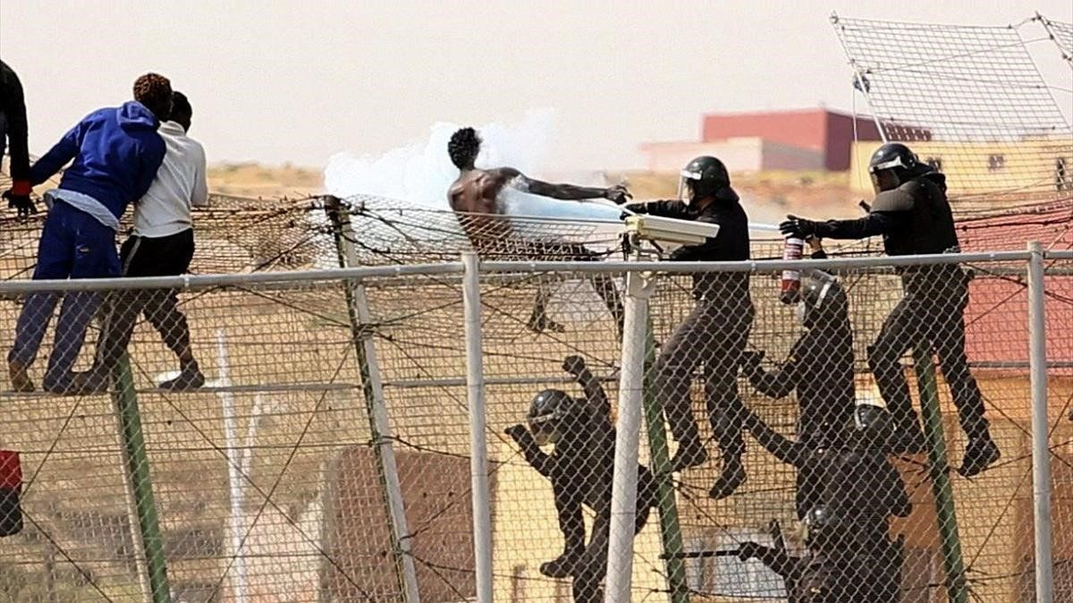 Guardias civiles rocían con un extintor a inmigrantes que intentaban usar mecheros en la valla de Melilla en una operación anterior.
