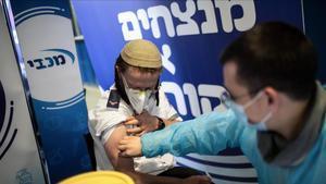 Un sanitario pone la vacuna a un hombre en un centro de vacunación en Jerusalén.