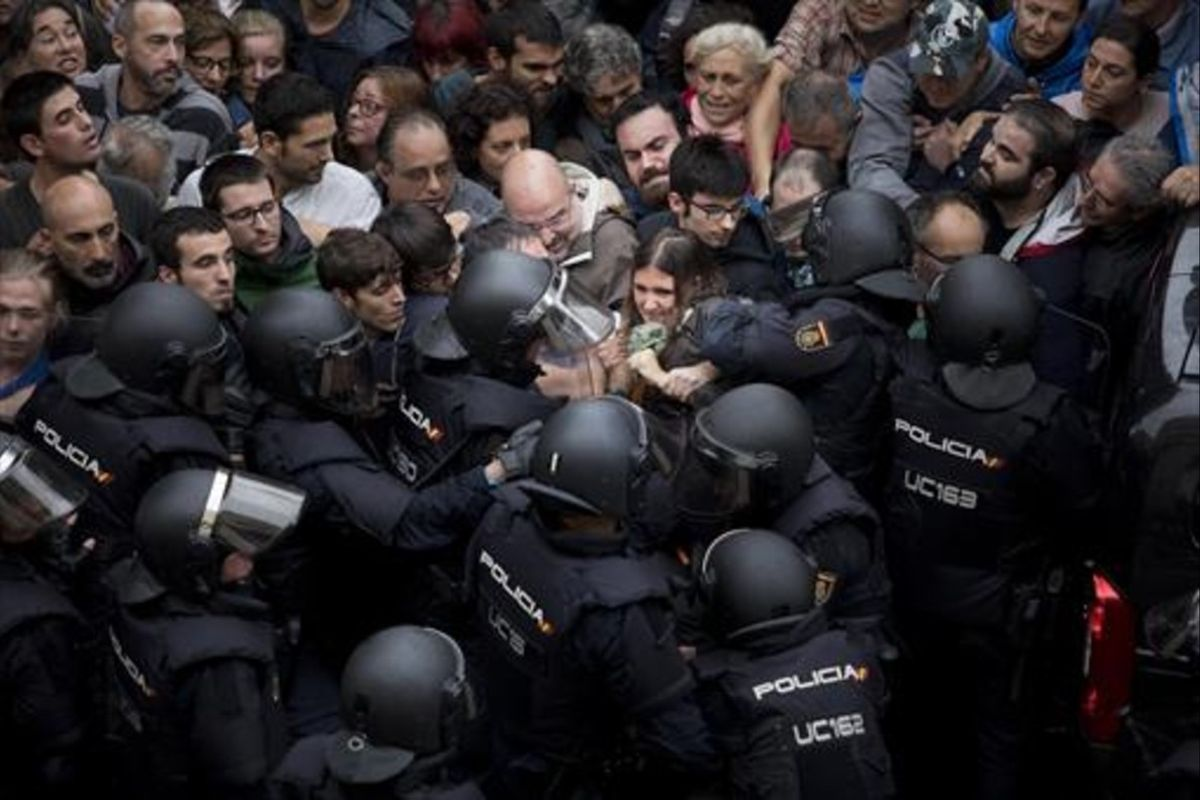 Agentes de la policía nacional intentan desalojar a las personas concentradas en las puertas del colegio Ramon Llull de Barcelona el 1-O.