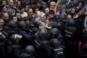 Agents de la policia nacional intenten desallotjar a les persones concentrades a les portes del col·legi Ramon Llull de Barcelona, l'1-O.