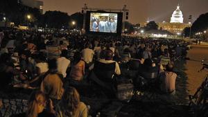 Ciclo de cine con el Capitolio de fondo, pantalla gigante y cinéfilos sobre césped.