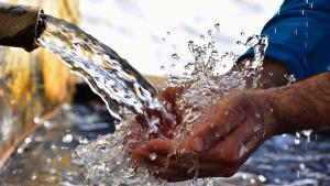 Un hombre se refresca las manos en una fuente.