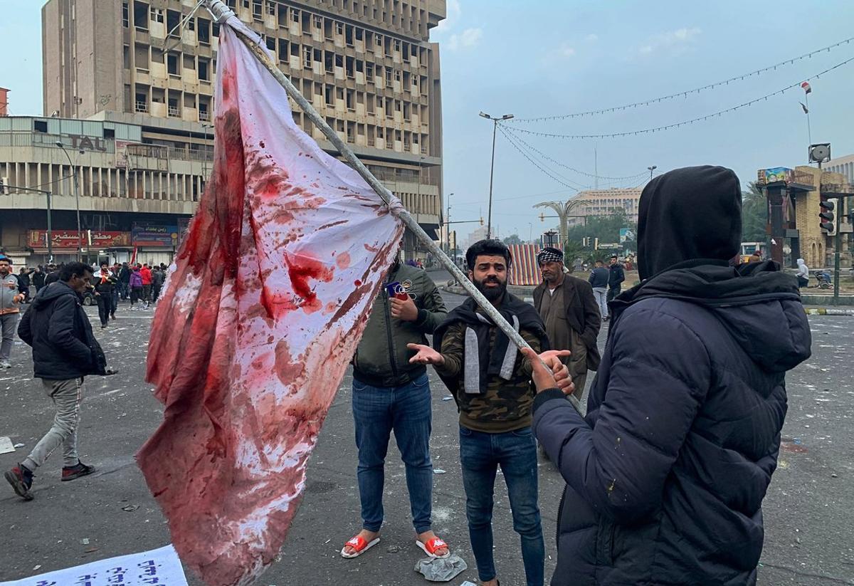 Manifestantes sostienen una bandera manchada de sangre tras el ataque en la plaza Al Jalani de Bagdad.