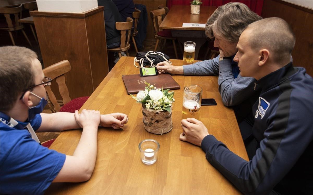 Seguidores del Hertha siguen el partido de su equipo, cerveza en mano, en un bar de Berlín.