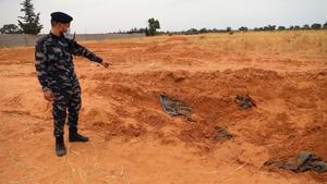 Un miembro de las fuerzas de seguridad leales al GNA señala una de las fosas comunes halladas en Libia en la ciudad de Tarhuna.