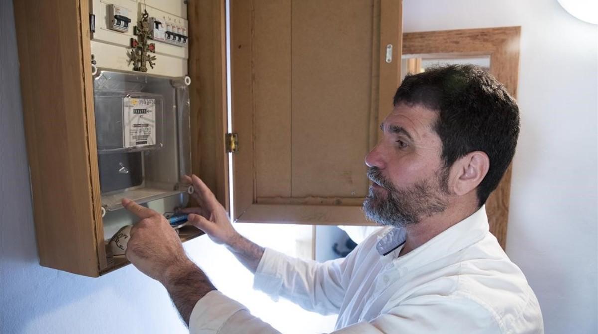 Pablo Álvarez inspecciona su contador eléctrico en su domicilio de Cornellà.