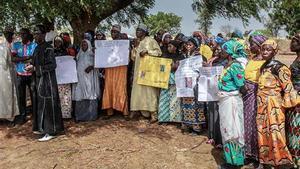 Los familiares sosteniendo los retratos de sus niñas durante una conmemoración cinco años desde que fueran secuestradas por el grupo yihadista Boko Haram