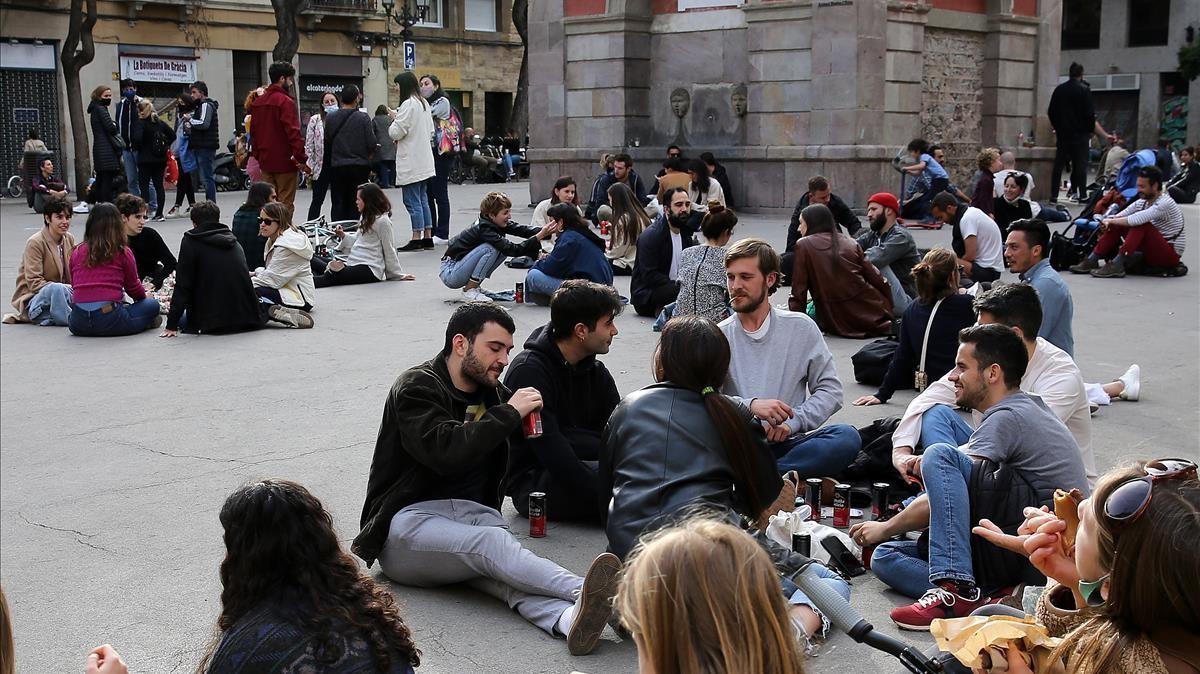 Grupos de jóvenes quedan para tomar algo en el suelo de la plaza de la Vila de Gràcia, en ausencia de bares y restaurantes por las tardes.