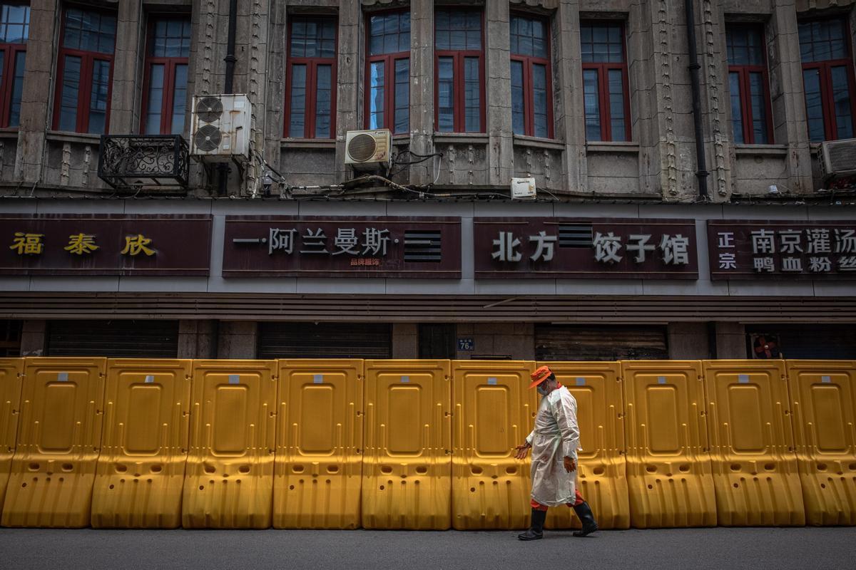 Un hombre camina frente a una de las barreras amarillas para separar zonas en Wuhan que se hicieron populares hace un año.