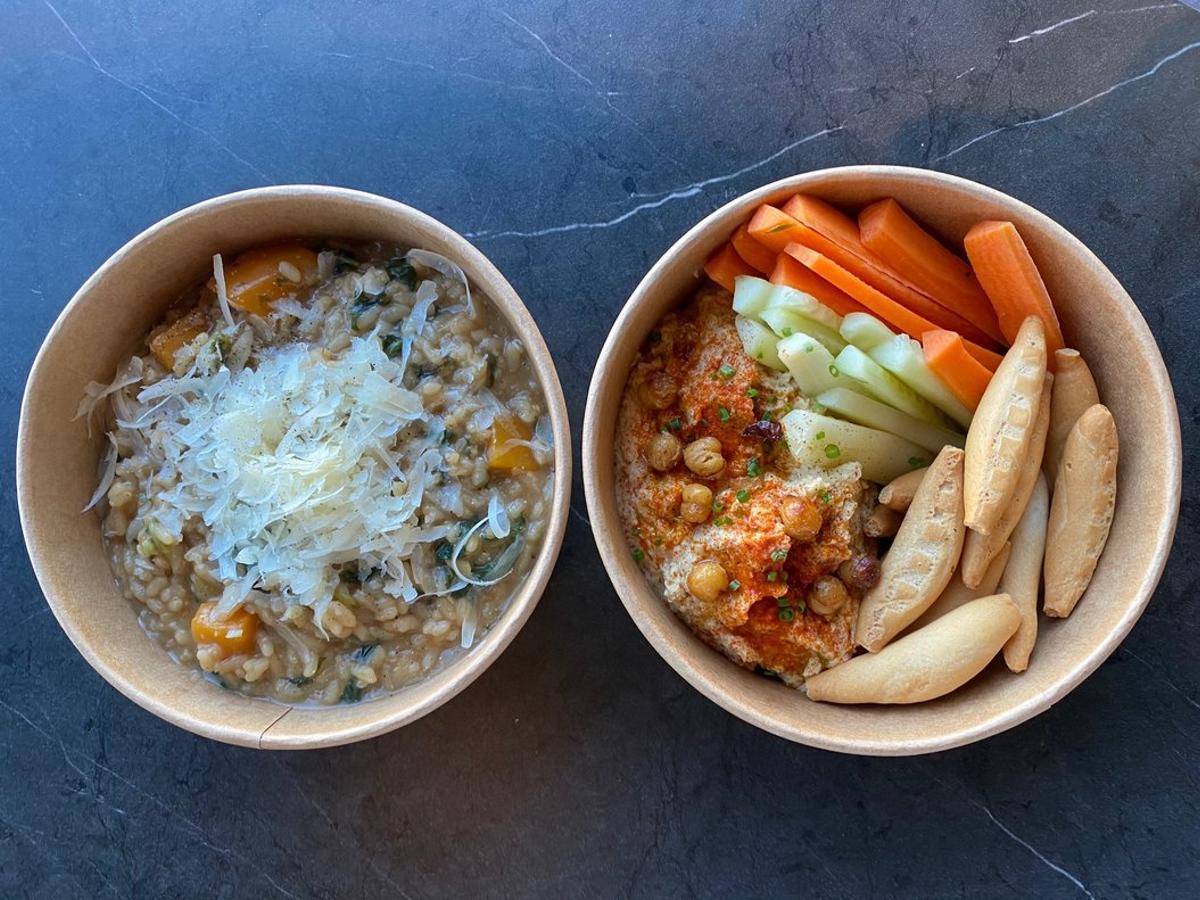 Dos platos del menú de mediodía para llevar y a domicilio de Arrozal Ca la Nuri: risotto de calabaza, espinaca y parmesano, y humus con crudités de verdura.