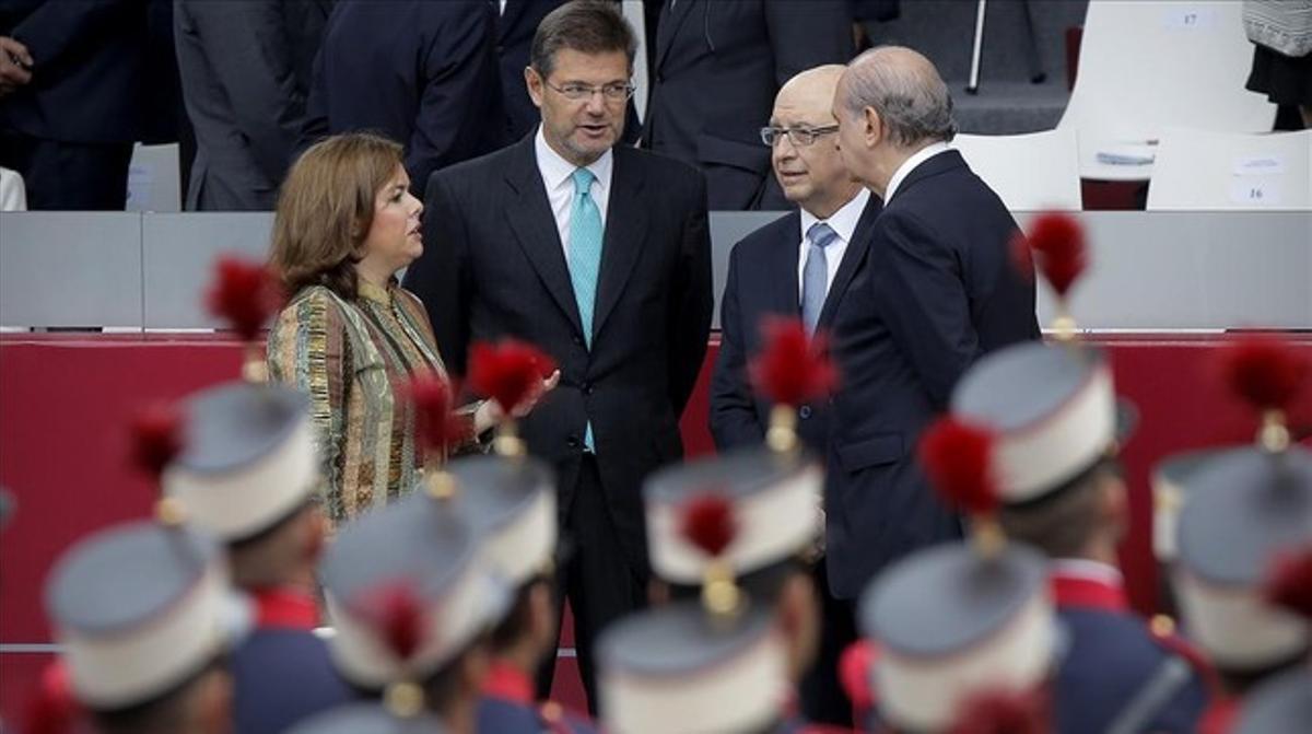 Cristóbal Montoro conversa con la vicepresidenta, Soraya Sáenz de Santamaría, y los ministros Rafael Catalá y Jorge Fernandez Diaz, durante el desfile del Día de la Hispanidad.
