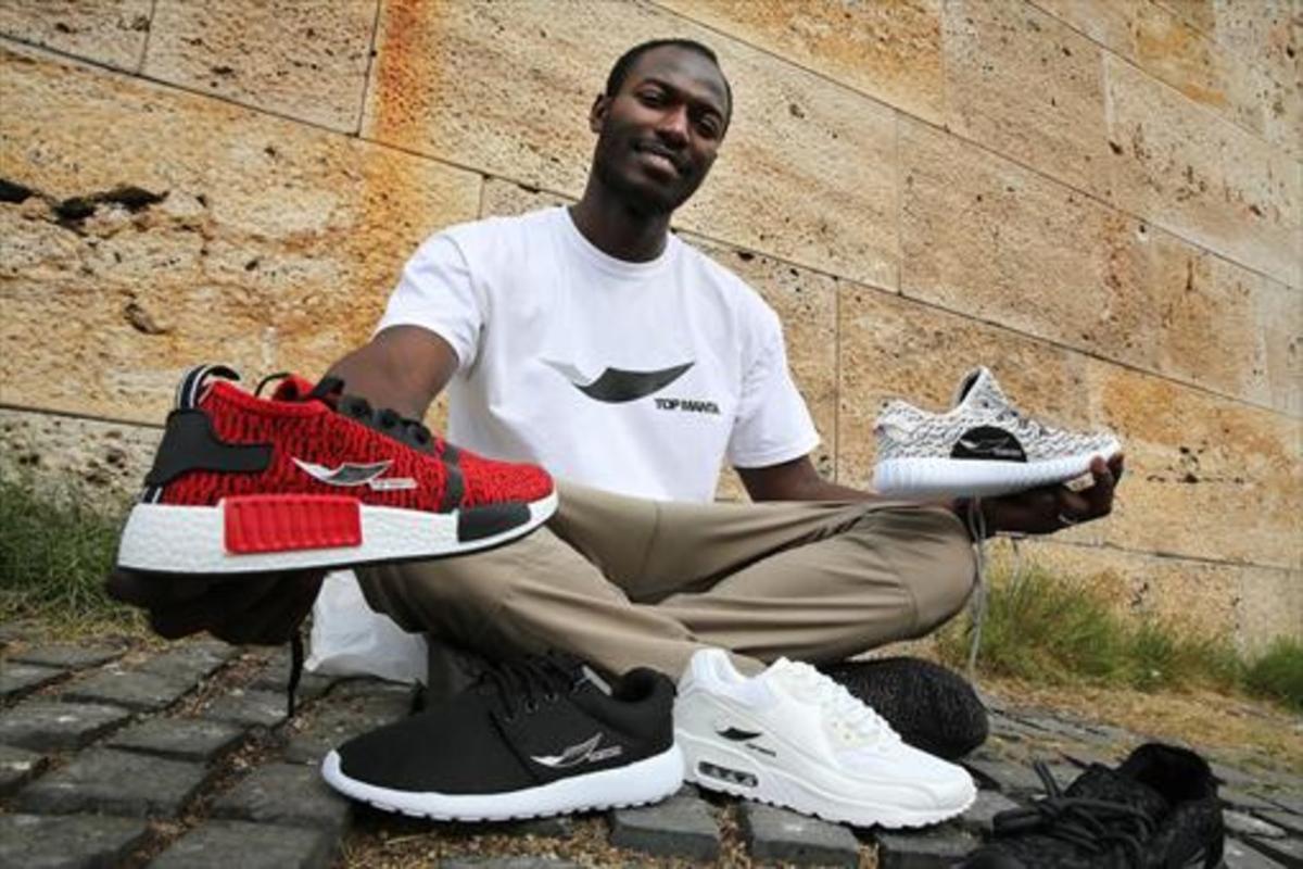 Aziz Faye muestra unas zapatillas de la marca 'Top Manta', cuyo logo está formado por una ola, un cayuco y una manta.