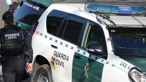 Unos agentes de la Guardia Civil salen del vehículo.