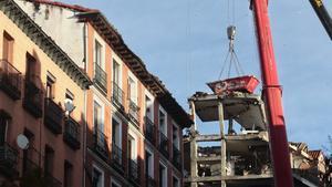 Una grúa durante el desmontaje del edificio siniestrado en el número 98 de la calle Toledo, en Madrid.