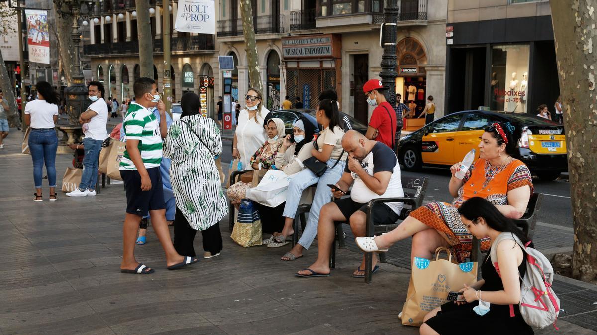 Turistas descansan en un banco de la Rambla, la semana pasada.