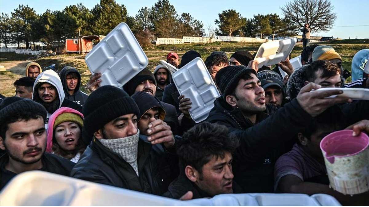 Guardacostas griegos cargan contra refugiados en la frontera turca. En la foto, un grupo de migrantes esperan que les sirvan comida en teritorio turco mientras esperan cruzar el río Meritsa para entrar en Grecia.