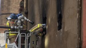 Una dotación de bomberos inspeccionan este jueves el exterior de la nave que se ha incendiado este miércoles en Badalona y que ha supuesto la muerte de al menos tres personas.