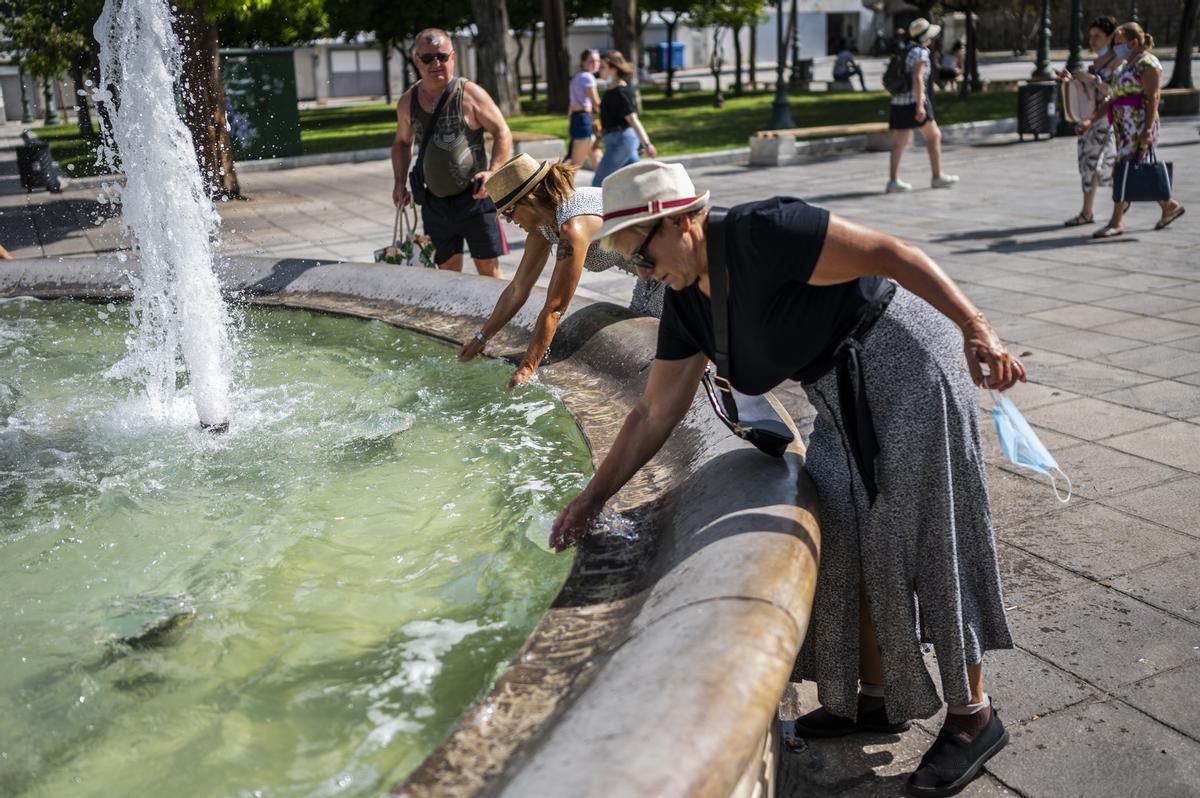 Unas mujeres se refrescan en la fuente de Syntagma Square en plena ola de calor en Grecia.