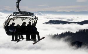 Un grupo de esquiadores y aficionados al snowboard suben en telesilla a la soleada cumbre del Feldberg (Alemania)