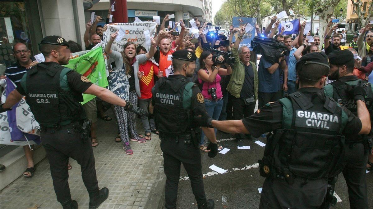 Guardias civiles ante un grupo de manifestantes, durante el registro del semanario 'El Vallenc'.