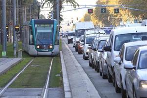 Un tranvía del Trambaix avanza por la Diagonal junto a una hilera de coches.