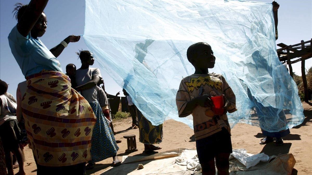 Una familiaestirando una red antimosquitos en Matongo (Zambia), en una imagen de archivo.