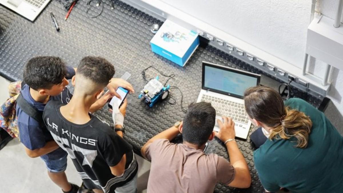 Jóvenes trabajando con aparatos electrónicos.