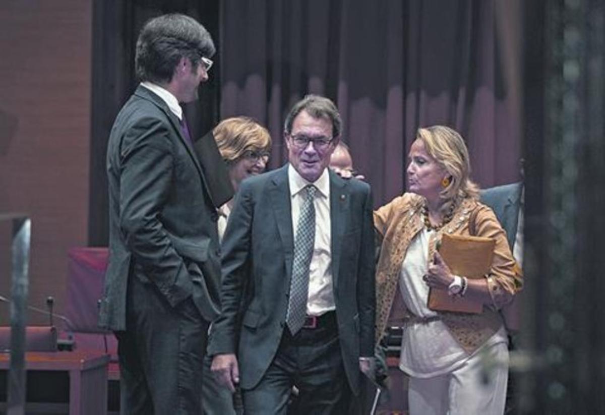 Artur Mas, juntoa su mujer y su jefe de prensa, se dirige al hemiciclo, ayer en el Parlament.