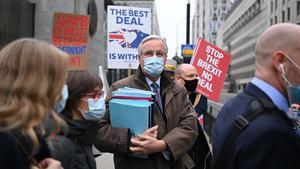 Manifestantes anti-'brexit' muestran pancartas al paso del negociador jefe de la UE, Michel Barnier, este lunes en Londres.