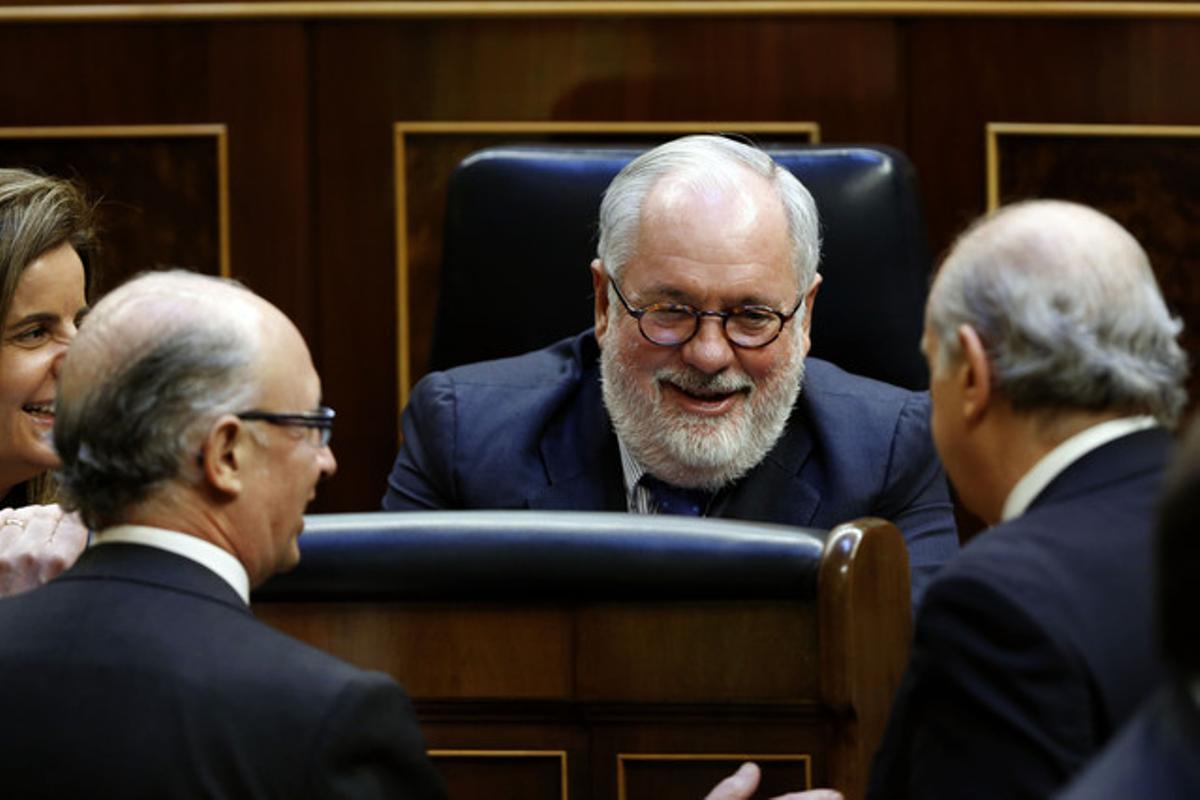 Miguel Arias Cañete, felicitado por los ministros Báñez, Montoro y Fernández Díaz, esta mañana, en el Congreso.