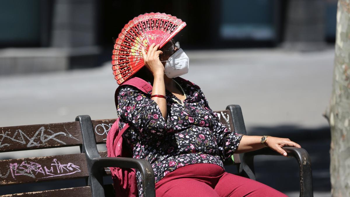 Una señora se protege del sol, ante la ola de calor, en las Ramblas de Barcelona.