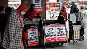 Una mujerprotegidacon máscarapasa junto a un kiosco que exhibe portadas sobre el impacto del coronavirus, en Londres.