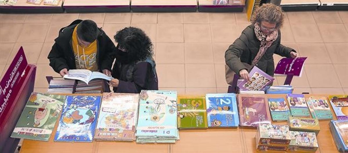 Unos clientes consultan libros de texto en una tienda Abacus, en Barcelona.