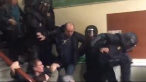 Un policía patea a las personas que estaban en la escalera del Institut Pau Claris el 1 de octubre del 2017.