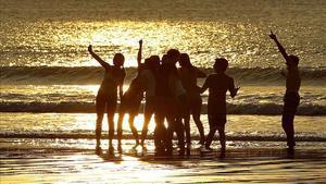 Un grupo de jóvenes disfruta del atardecer en la playa de La Concha de San Sebastián.