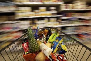 Carro de la compra lleno de productos en un supermercado.